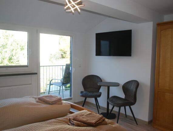 Hier sehen Sie den Schlafbereich inklusive der modernen Sitze, TV und Beistelltisch des Ferienzimmers. Das ganze wird abgerundet mit dem angeschlossenen Balkon.